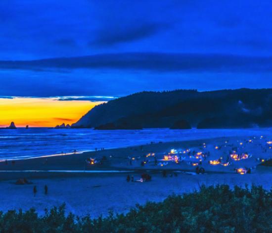 Beach at dusk with many bonfires