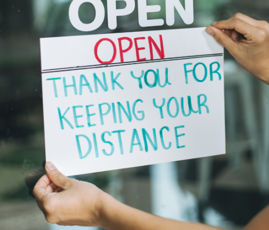 """image: storefront sign """"open, thank you for keeping your distance"""""""